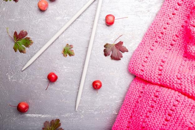 編み針の近くのピンクのスカーフ