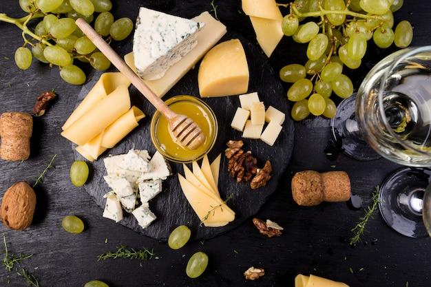 チーズプレート。クルミとチーズの品揃え、石のスレート板に蜂蜜をパンします。