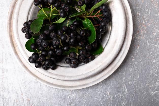 Черноплодная рябина в серебряной металлической миске. арония ягодная с листиком.
