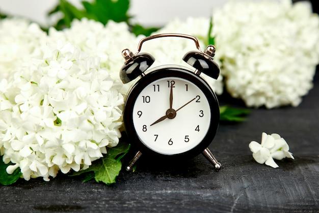 黒の目覚まし時計と黒の白い花。