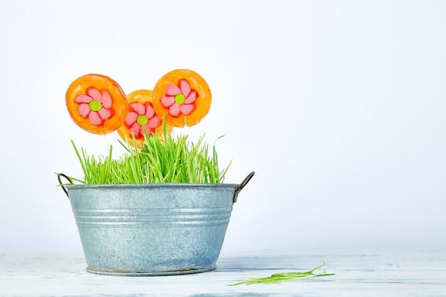 春のコンセプト。草と植木鉢にキャンディロリポップの花。コピースペース。