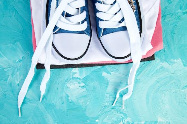 女性のスニーカーの靴とティーのフラットレイアウト