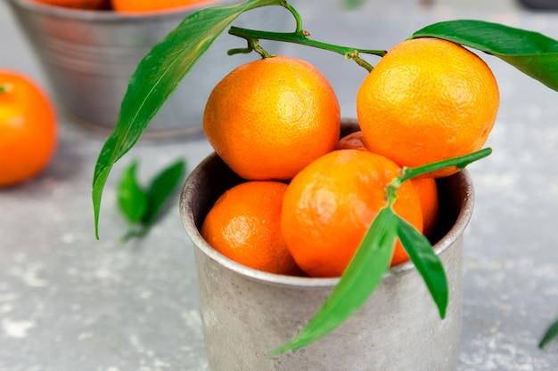 かごの中の新鮮なみかん。皮をむいて、灰色の背景にタンジェリンオレンジをスライスしました。柑橘類の背景。大きい。