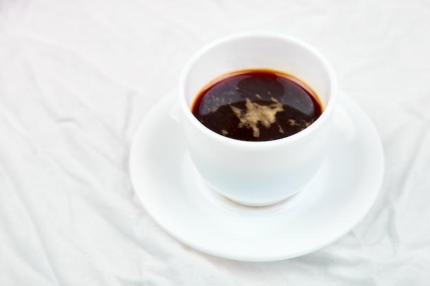 Одна чашка кофе на белой кровати.