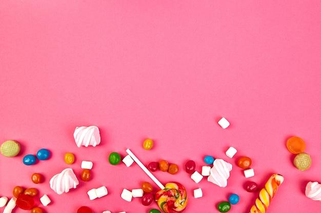 Разноцветные конфеты на розовом