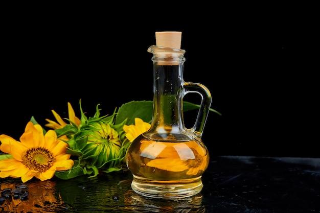 Подсолнечное масло в стеклянной банке, семена и цветы