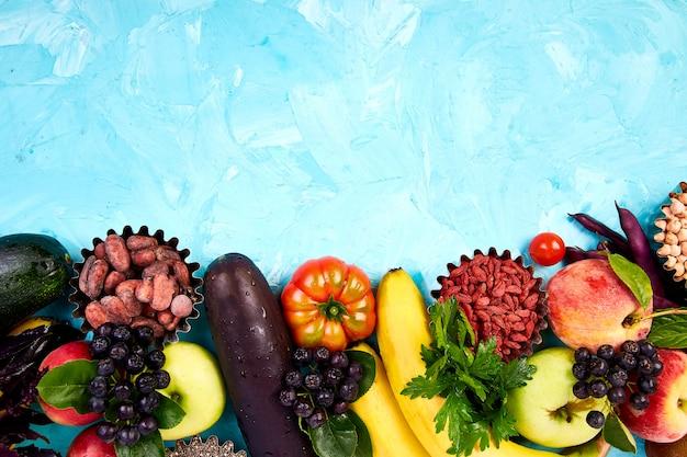 ビーガンデトックス。スーパーマーケット製品。青色の背景に健康的なカラフルな食べ物