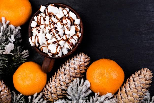 黒い表面に茶色のカップでチョコレートとクリスマスフード甘いマシュマロフラットレイアウト