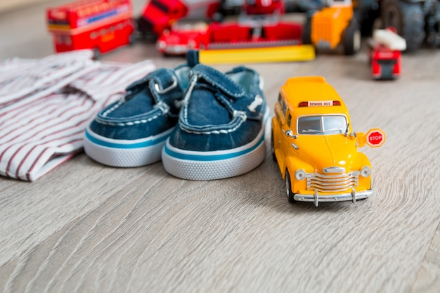 シャツと灰色の木製の表面に青いボートシューズの近くのスクールバスのおもちゃ少年の衣装をクローズアップ