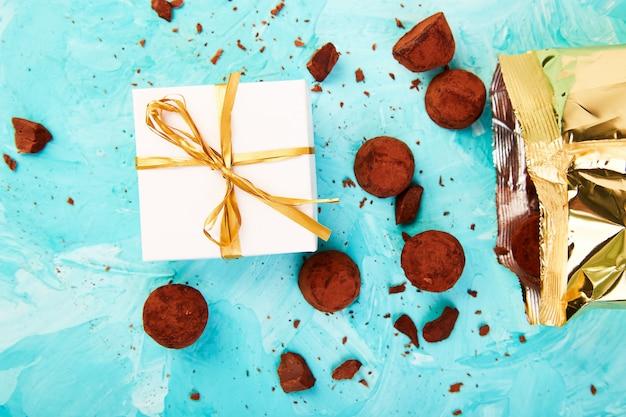 Шоколадные конфеты трюфели выпадают из золотой роскошной коробки