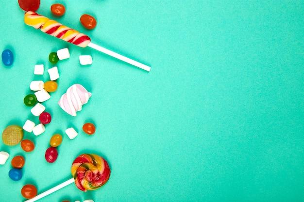 Разноцветные конфеты на пастельных бирюзовых. плоская планировка