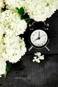 Черный будильник и белые цветы на черном.