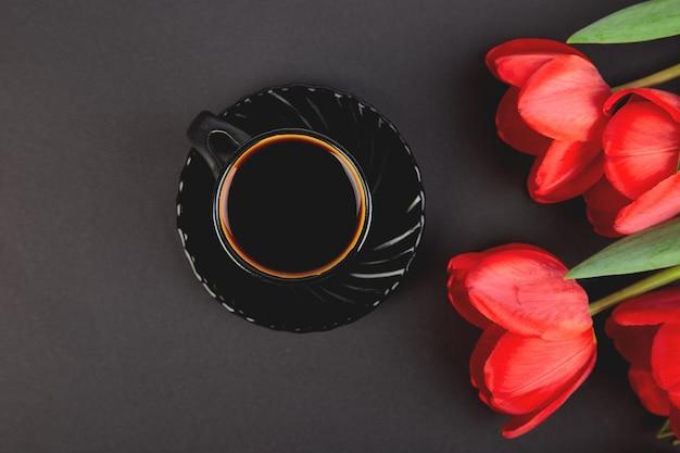 赤い花束チューリップと黒のコーヒーカップ。平干し。母または女性の日。グリーティングカード。おはようございます。コピースペース。春。
