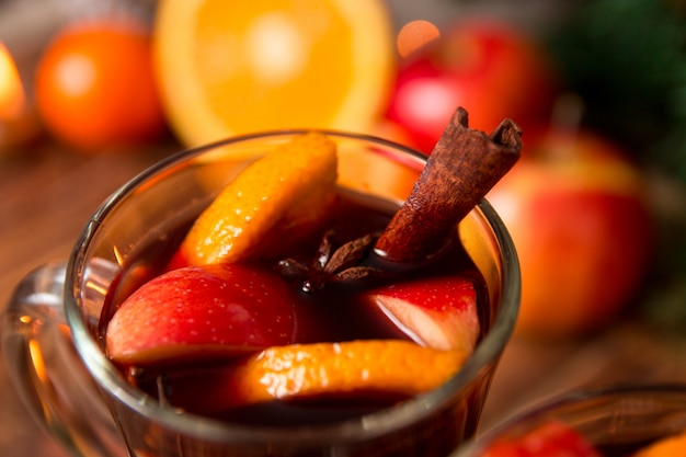 フルーツ、キャンドル、スパイスとクリスマスのグリューワインのクローズアップ。