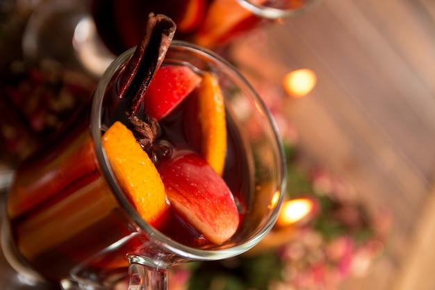 クリスマスフルーツ、キャンドルとホットワインのクローズアップ。