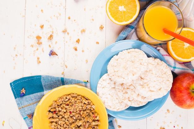 健康的な朝食。さまざまな品揃えセット。オレンジジュース、グラノーラ、コーヒー、フルーツ。