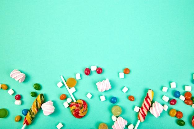 Красочные конфеты на пастельных бирюзовом фоне. плоская планировка