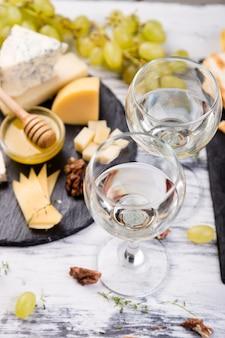 チーズプレート。クルミとチーズの品揃え、石のスレートプレートに蜂蜜をパンします。
