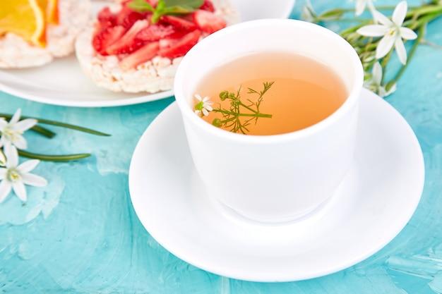 Завтрак - чай, рисовые хлебцы со свежими фруктами на синем фоне.