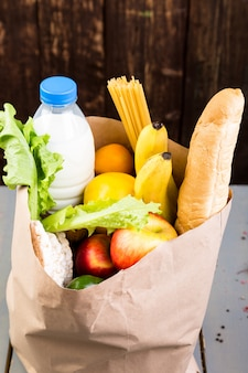 食料品の買い物 。木製の背景の紙袋にさまざまな食品。