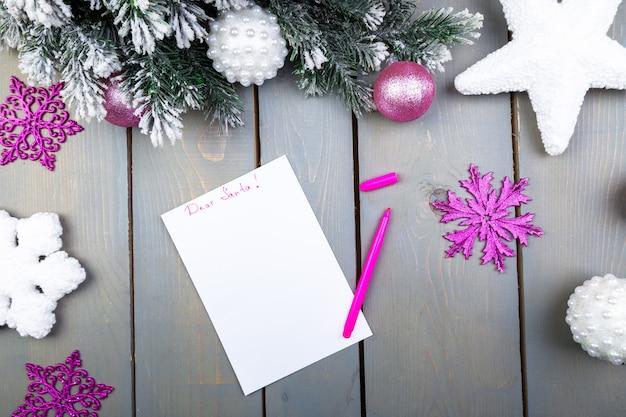 Лист бумаги, розовые карандаши и рождественские украшения на деревянном фоне. нового года и рождества. вид сверху. плоская планировка