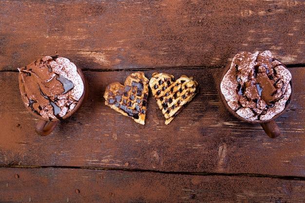 ベルギーのハート形の木製の背景にマシュマロとホットチョコレートのワッフル。