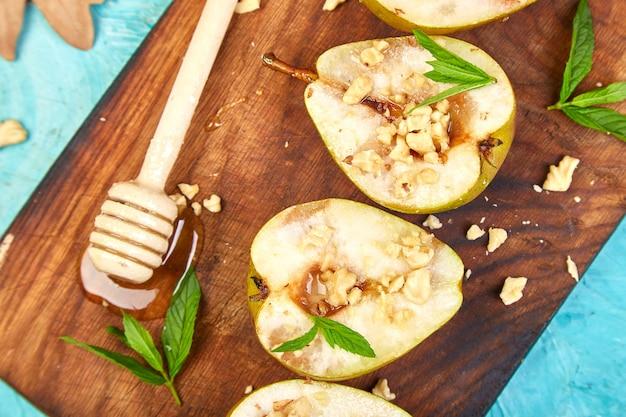おいしいロースト梨と蜂蜜とクルミの青い背景のテーブル。
