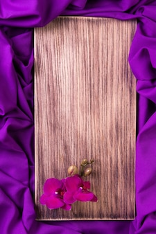 Фиолетовая орхидея на деревянных фоне.
