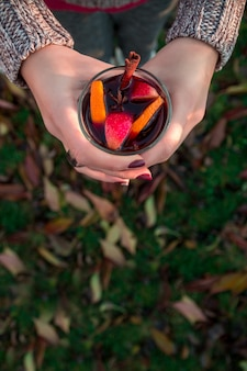 Глинтвейн в руке женщина на фоне осенних листьев. горячий рождественский напиток.