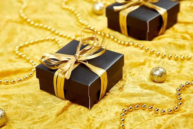 ゴールドリボンと豪華な黒のギフトボックス