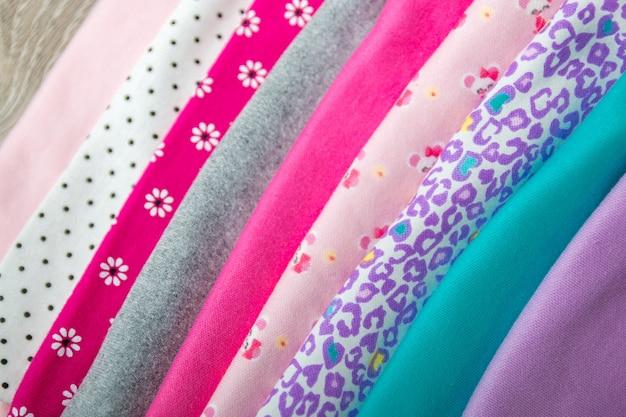 Ткань швейная. сложенный розовый и белый комбинезон на нем на сером фоне деревянных.