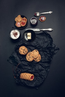 一杯のコーヒー、チョコレートクッキーと黒いテーブルの上のビスケットとカプチーノ