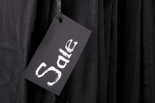 黒のズボンとジーンズの背景に販売に署名します。