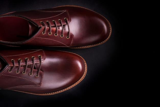 Коричневые ботинки оксфорда на черной предпосылке.