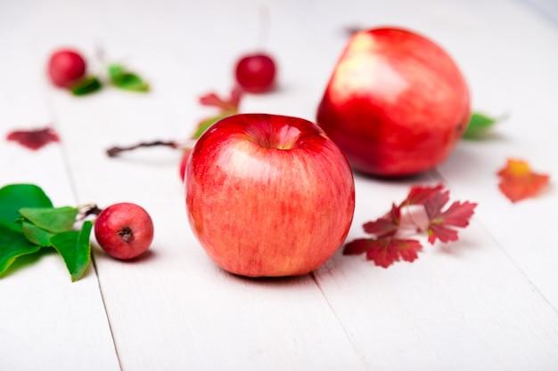 白い木製の大小の赤いリンゴ。閉じる。秋。
