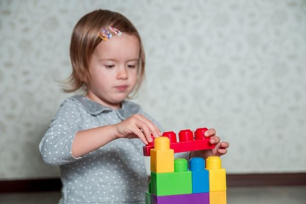 Ребенка девушка весело и построить из ярких пластиковых строительных блоков. малыш играет на полу. развивающие игрушки. раннее обучение.