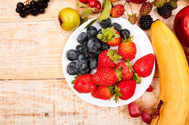 白い木製の背景上の果物のフラットレイアウト。