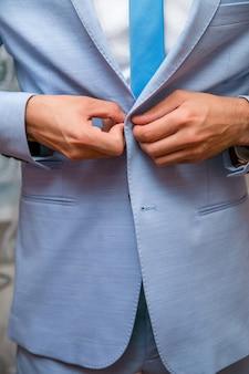 ビジネスマンは青いジャケットを着ています。新郎の朝の準備。
