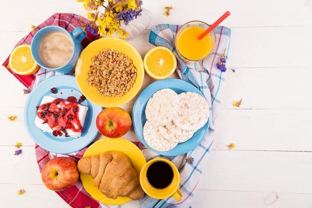 健康的な朝食。さまざまな品揃えセット。オレンジジュース、グラノーラ、クロワッサン、コーヒー、フルーツ。