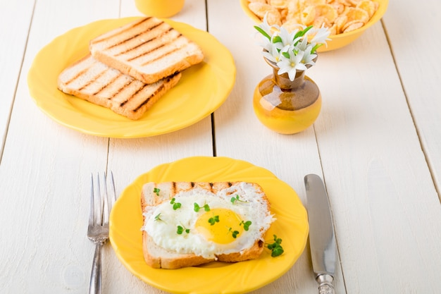 白い木製の花と花瓶の近くの黄色いプレートに卵とトーストします。健康的な朝食。