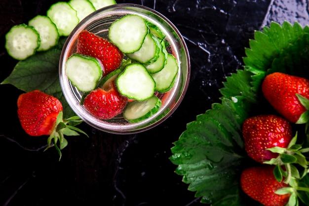 黒のガラスにキュウリとイチゴのデトックス水。ダイエット。上面図。