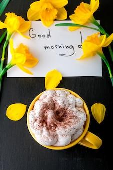 黄色の水仙の花と引用符でコーヒーマグカップおはよう黒いテーブルに。母の日または女性の日。グリーティングカード。上面図。朝ごはん。
