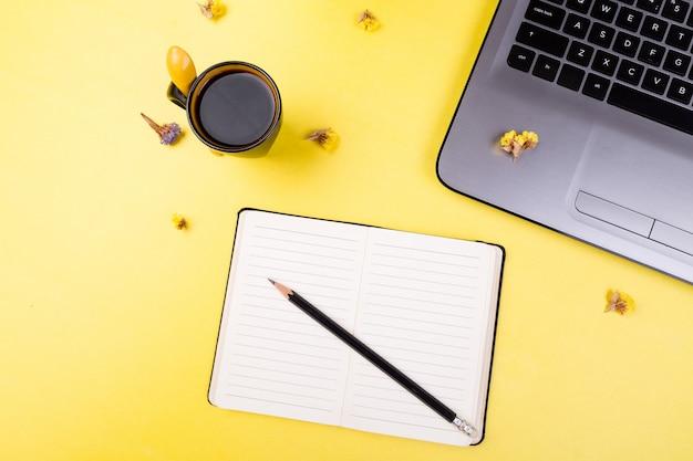 ノートブック、コーヒー、黄色の女性の家庭やオフィスの職場のための花。上面図。コピースペース