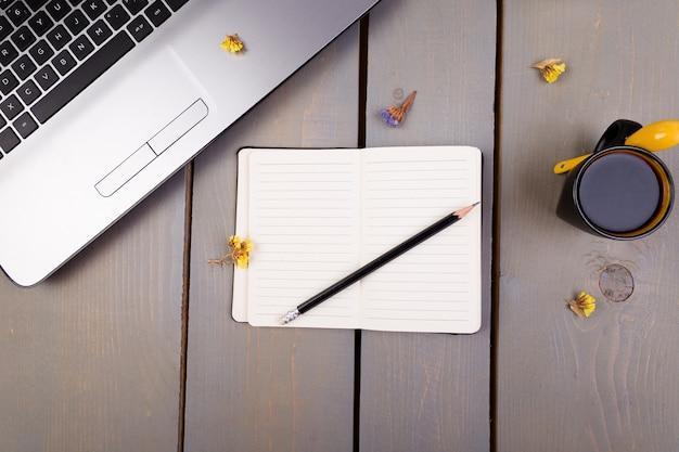 ノートブック、コーヒー、木製の女性の家庭やオフィスの職場のための花。上面図。コピースペース