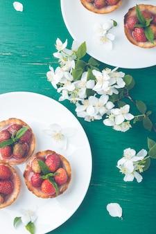緑の白い皿にイチゴのタルト。上面図。トーンの写真。花が飾られています。