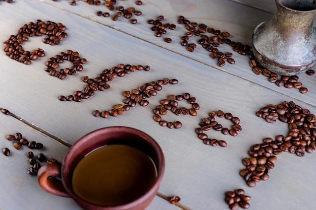 コーヒーの碑文。カップの近くのテーブルの上の単語コーヒー。平干し。