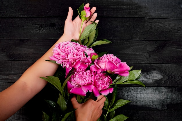 Руки флорист женщины держа красивый букет пионов.