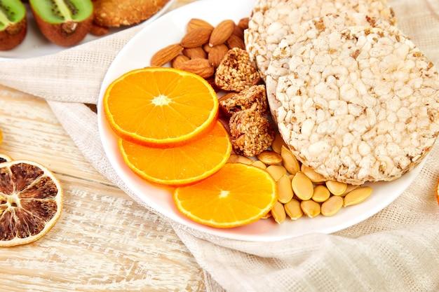 Полезные закуски - батончик из овсяной мюсли, рисовые чипсы, миндаль, киви, сушеный апельсин