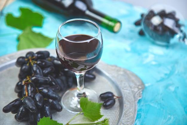Концепция красного вина с бутылкой, бокалом и виноградом