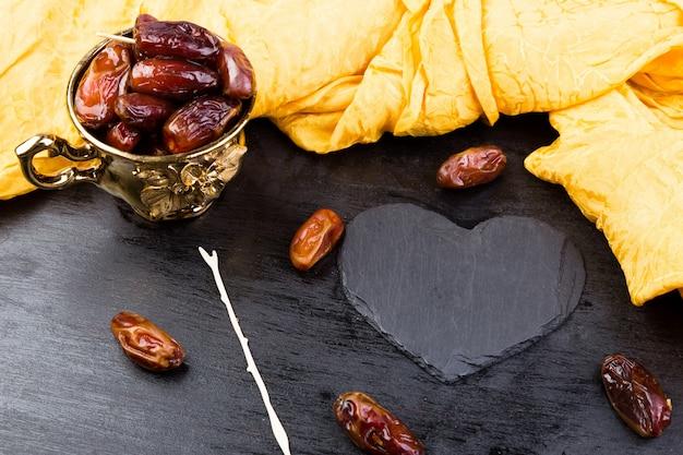 Сухофрукты финики в золотой чашке возле сланца черного сердца.